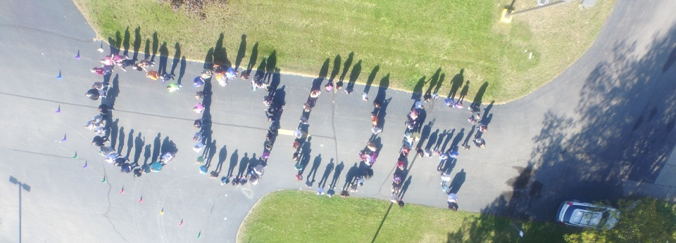 aerial photo of students outside the school building, in formation to spell COOR