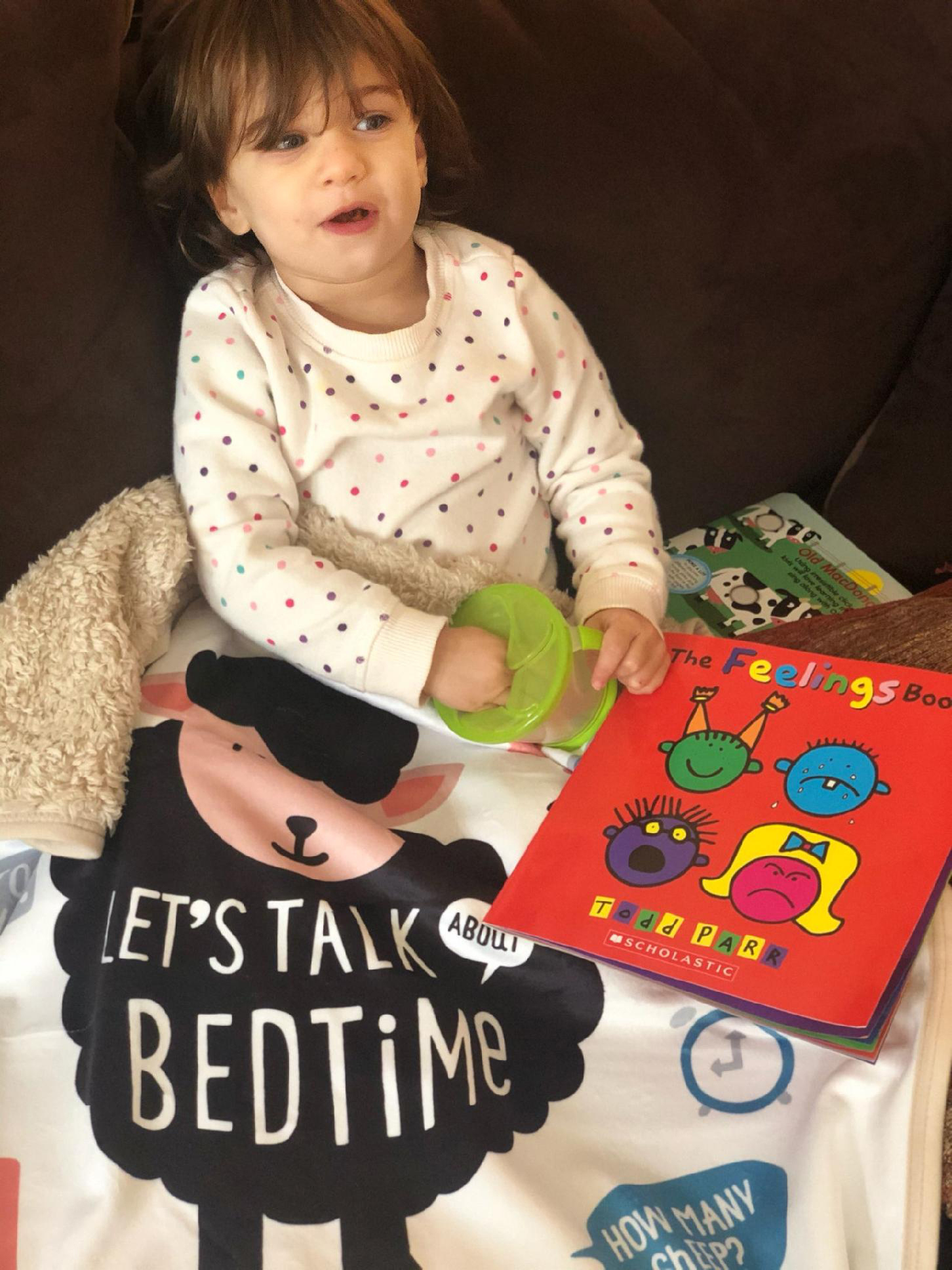 toddler with blanket and books